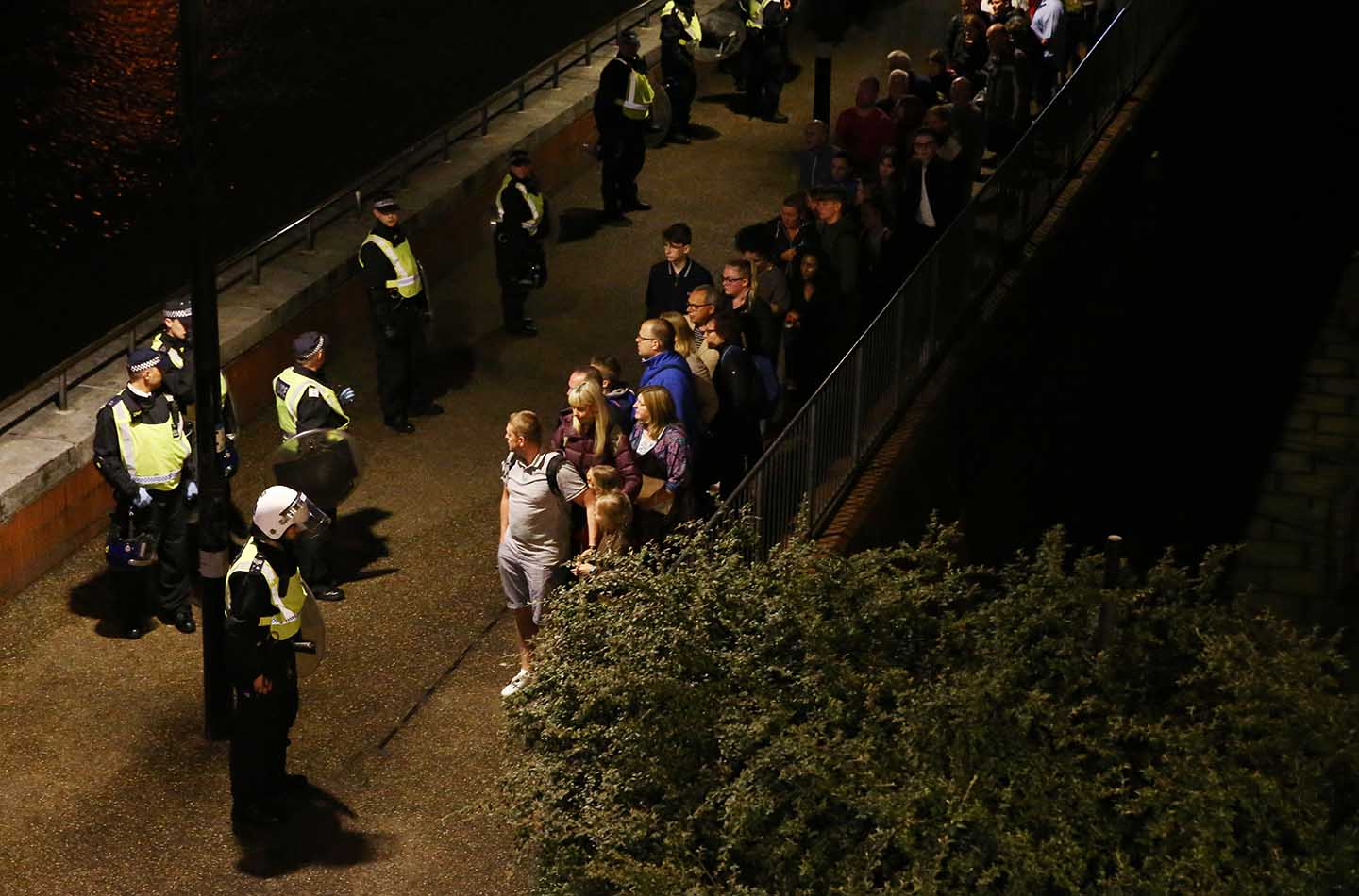 Police officers stand with people evacuated from the area after an incident near London Bridge in London